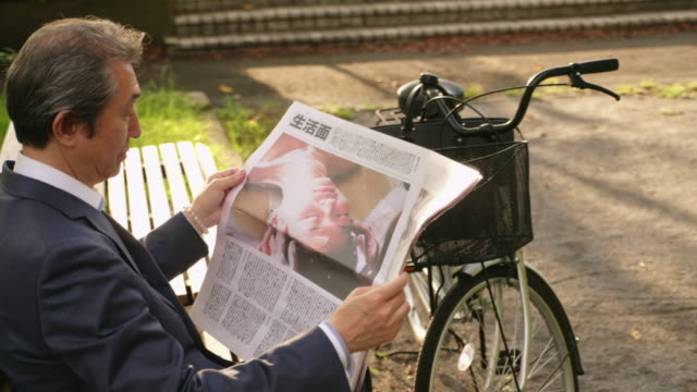 japanese businessman with a newspaper - newspaper headline stock videos & royalty-free footage