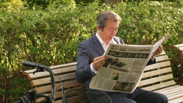 新聞を日本のビジネスマン - ベンチ点の映像素材/bロール
