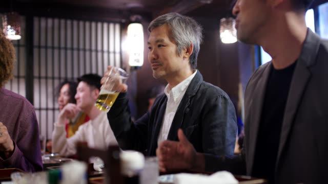 居酒屋でメニューを見ている日本のビジネスマン - 居酒屋点の映像素材/bロール