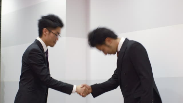 MS Japanese businessmen shake hands and bow / Tokyo, Japan