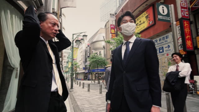 japanese businessmen talking in street - 保護マスク点の映像素材/bロール
