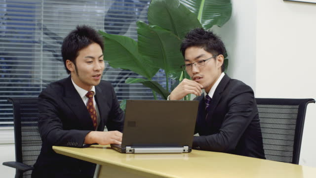 MS, PAN Japanese businessmen using laptop in office / Tokyo, Japan