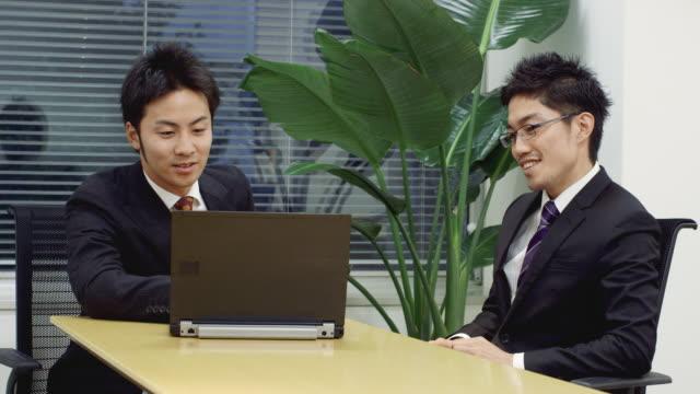 MS Japanese businessmen using laptop in office / Tokyo, Japan