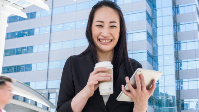 japanese businesswoman using digital tablet in the street - only japanese stock videos & royalty-free footage