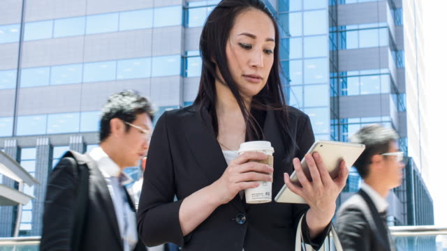 japanese businesswoman using digital tablet in the street - convenience stock videos & royalty-free footage