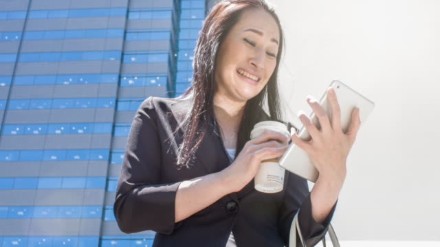 Japanese businesswoman using digital tablet in the street