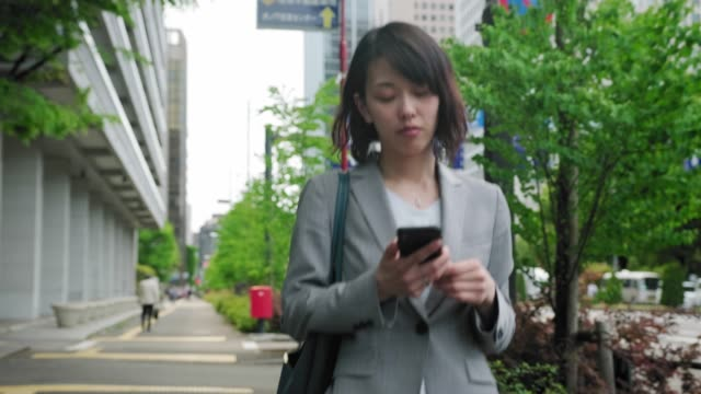 vídeos de stock e filmes b-roll de japanese businesswoman using smart phone on the go - leste