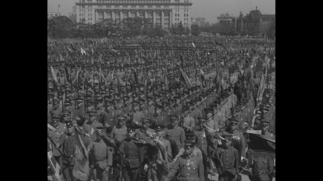 japanese cadets stand in formation on huge field / emperor hirohito rides a white horse as he rides onto grounds with military officers for review of... - 昭和天皇点の映像素材/bロール