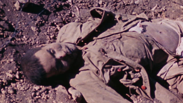 japanese casualty lying where he fell, and marine walking past toward ridge with rocky outcropping and two parked jeeps / iwo jima, japan - 硫黄島の戦い点の映像素材/bロール