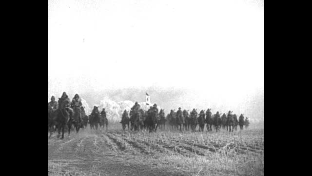 japanese cavalry approaches at a trot with japanese flag borne in midst of group as japanese army moves toward chinchow / note exact day not known - 偶蹄類点の映像素材/bロール
