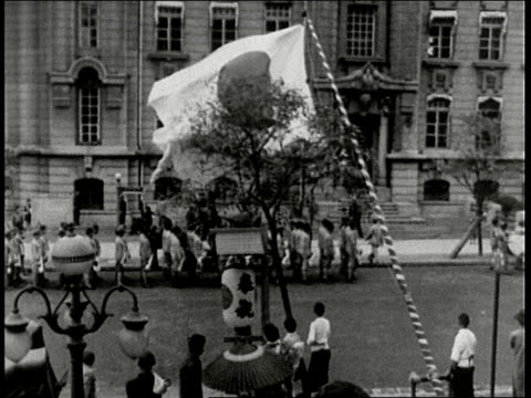 japanese celebrate anniversary of country's occupation with large flag waving and men doing dancing with fighting sticks / manchuria - anno 1938 video stock e b–roll