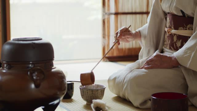 vídeos y material grabado en eventos de stock de ceremonia japonesa anfitrión medición de agua en la taza de té - sado