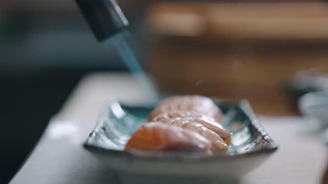 vídeos y material grabado en eventos de stock de chef japonés haciendo blowtorch aburi salmón nigiri - preparación de alimentos