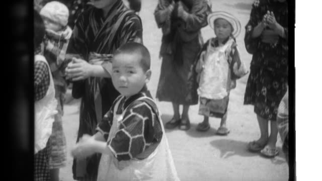 vidéos et rushes de japanese children dance, nap, and watch a picture show at a nursery school; nurses feed milk and snacks to babies; and farming housewives plant rice. - napping