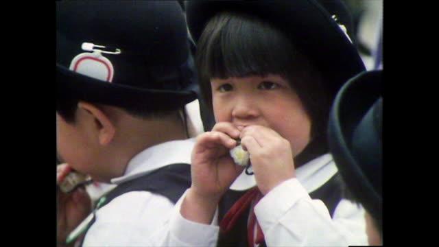 vidéos et rushes de japanese children eating lunch at shrine in tokyo; 1981 - cartable