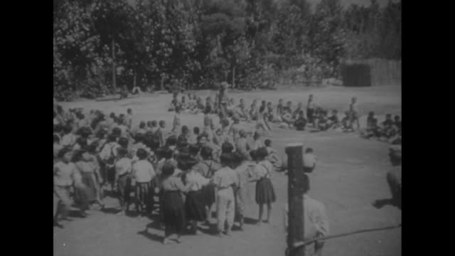 japanese children playing and doing calisthenics on okinawa playground under supervision of us marines / note: exact day not known - guerra del pacifico video stock e b–roll