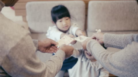 vídeos de stock e filmes b-roll de japanese children receiving money from grandparents (otoshidama) - making money