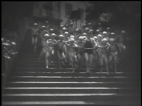 1939 montage japanese children running and jumping on springboard, running down stairs in swimming suits with an adult, and running through shower room with suits on and a beach ball / japan - kinder beim duschen stock-videos und b-roll-filmmaterial