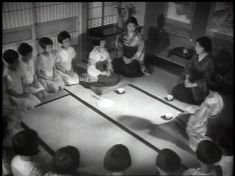 1939MONTAGE Japanese children sewing at machines and sitting in a circle practicing the tea ceremony with women / Japan
