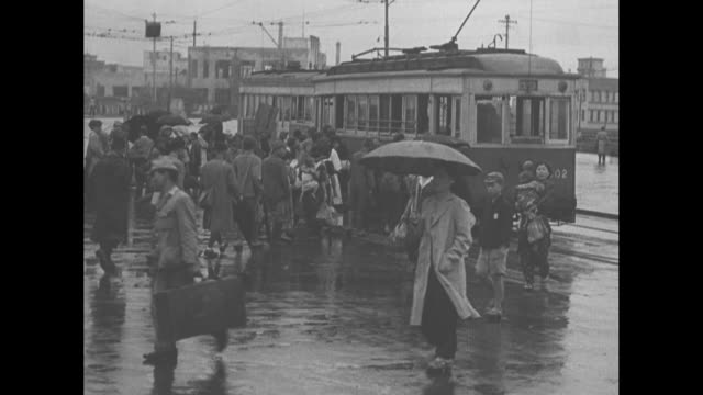 japanese citizens with umbrellas on rainslick road / train comes to stop in rail station / people walking past as others board streetcar / american... - 1940~1949年点の映像素材/bロール