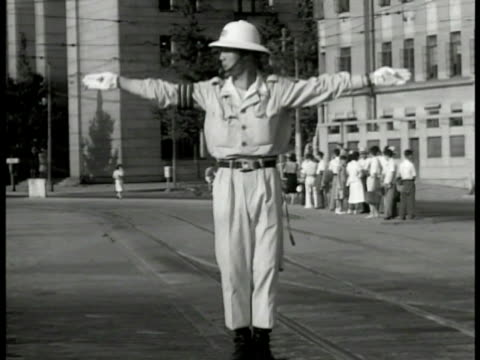 japanese city street ms japanese traffic cop directing ws cars and bicycle carriages passing cu street sign 'ginza ave z ave' ws japanese soldiers in... - 1940~1949年点の映像素材/bロール