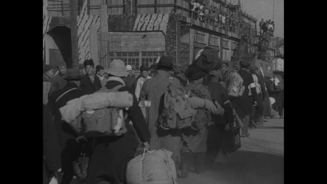 japanese civilians carrying luggage walking along pier and up gangway to ship as they leave china to return home to japan after world war ii / note:... - guerra del pacifico video stock e b–roll