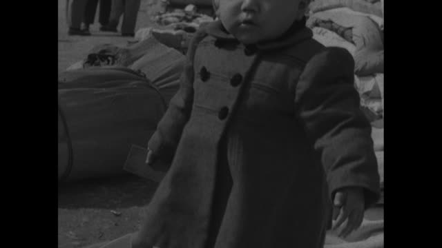 japanese civilians in embarkation area guarded by chinese soldiers / two shots of japanese child surrounded by peoples' belongings / japanese... - stillahavskriget bildbanksvideor och videomaterial från bakom kulisserna