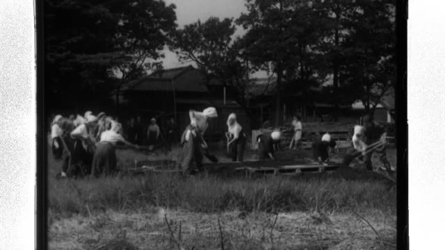 japanese civilians, mostly women, maintain air raid warning devices, dig shelters, conduct drills, fight fires, and plant yard gardens to aid in the... - pianificazione di emergenza video stock e b–roll