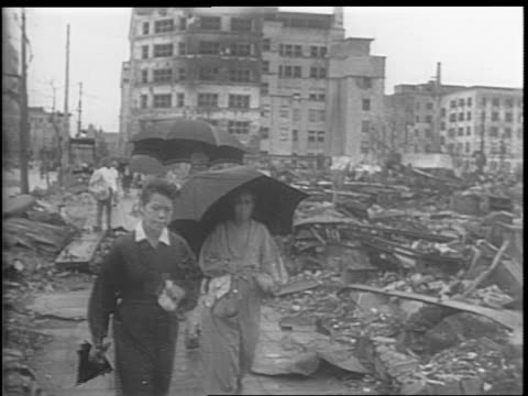 japanese civilians walk through the bombed-out streets of tokyo, montage of stacks of rubble and wreckage / montage of emperor hirohito's undamaged... - 空爆点の映像素材/bロール