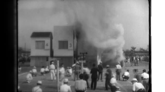 Japanese civilians watch a demonstration in which four new wooden houses are set ablaze three burn rapidly while an experimental version resists the...