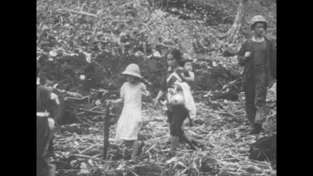 japanese civilians who have surrendered walking along path with us marines / japanese civilians walking across field with marines / two shots of... - pacific war video stock e b–roll