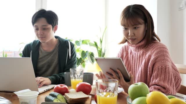 vídeos y material grabado en eventos de stock de pareja japonesa en casa, comiendo juntos y utilizando tecnologías para el trabajo remoto. mujer japonesa leyendo e-book - exclusivamente japonés