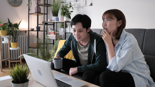japanese couple at home, using video call to attend business meeting - married stock videos & royalty-free footage