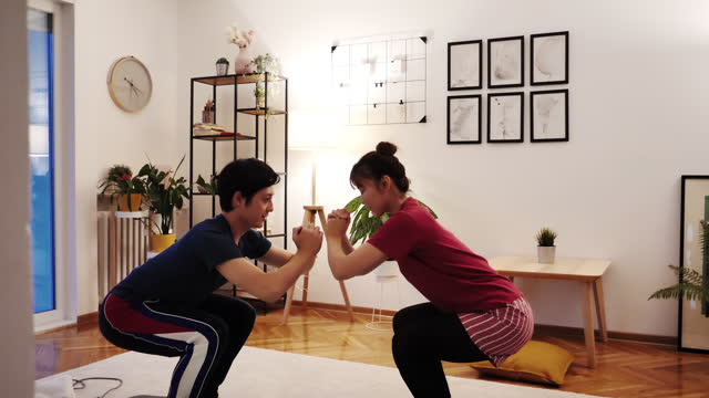 japanese couple exercising at home, doing squats with online fitness trainer during quarantine - crouching stock videos & royalty-free footage