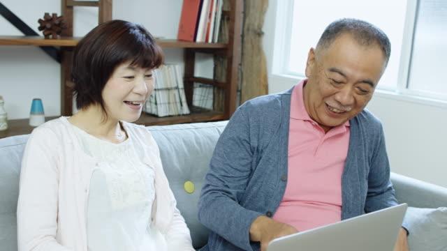 ノート パソコンの画面で笑って日本人夫婦 - ノートパソコン点の映像素材/bロール