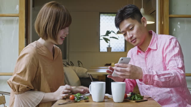 朝食を食べながら携帯電話を共有する日本人カップル - 見せる点の映像素材/bロール