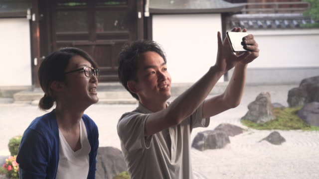 japanese couple taking picture with smartphone - photographing self stock videos & royalty-free footage