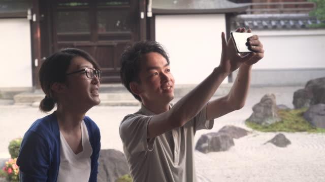 日本語スマート フォンで写真を撮るをカップルします。 - 自分撮り点の映像素材/bロール