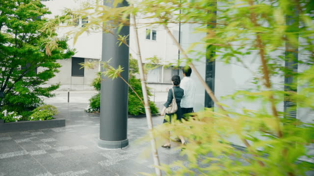 建物に沿って歩いて ws 日本人夫婦 - istockalypse点の映像素材/bロール