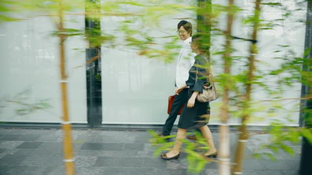 建物の前を歩いて ws 日本人夫婦 - istockalypse点の映像素材/bロール