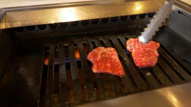 """japanese cuisine - """"yakiniku"""" which means """"grilled meat"""". - fleischzange stock-videos und b-roll-filmmaterial"""