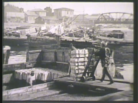 japanese dock workers loading supplies, crates, on dock. mitsubishi warehouse' on pier, fisherman on boat lower fg. ships in harbor. - warehouse点の映像素材/bロール