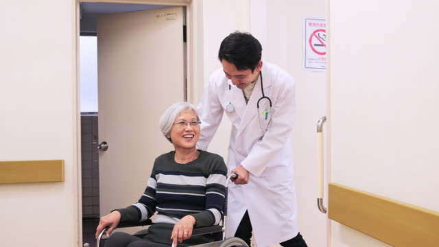 japanese doctor conversing with patient in wheelchair - medical condition stock videos & royalty-free footage
