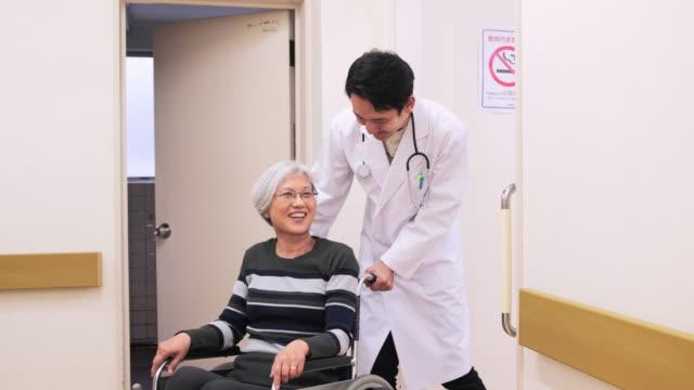 vídeos de stock, filmes e b-roll de médico japonês conversando com paciente em cadeira de rodas - condição médica