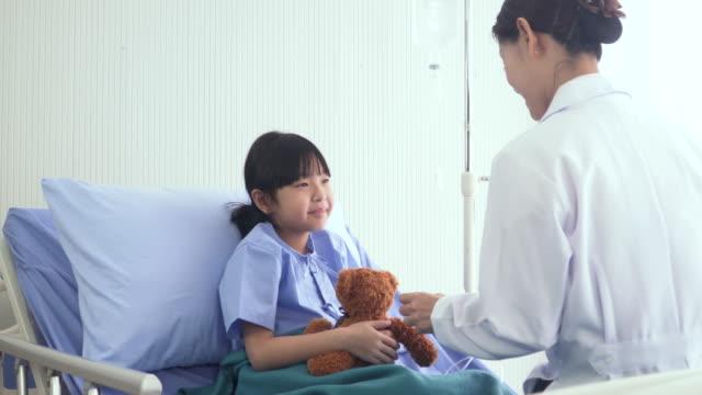 日本人医師は病棟でデジタル タブレット上のタイの女の子の病気のチェックに来ています。 - 女医点の映像素材/bロール
