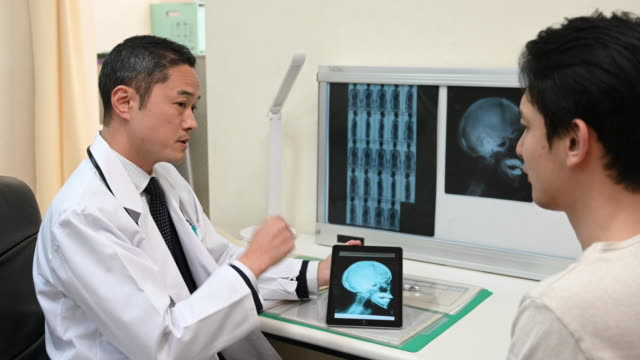 japanese doctor showing patient x ray on digital tablet patient - medical procedure stock videos & royalty-free footage