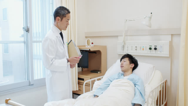 病院のベッドの患者に話す日本の医者 - 健康診断点の映像素材/bロール