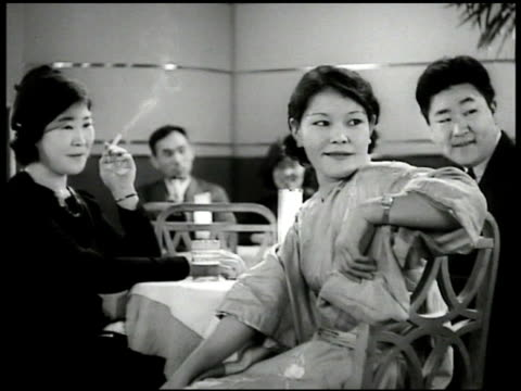 vídeos de stock, filmes e b-roll de japanese eating in restaurant japanese female serving man she thinks is ethiopian policeman wiping make-up off japanese male pretending to be of... - 1935