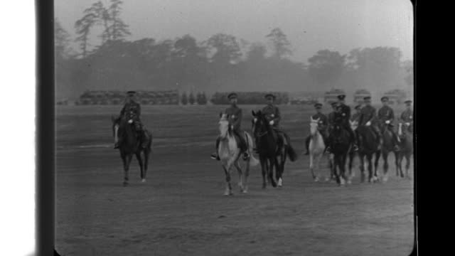 Japanese Emperor Hirohito on horseback reviews marching troops on his birthday airplanes fly in formation light tanks and cavalry pass by kicking up...