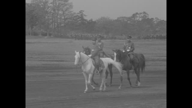 Japanese Emperor Hirohito rides on white horse accompanied by military officers on horseback during military review / color guard with rifles and...